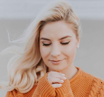 blonde haired woman in orange knitted long sleeved top