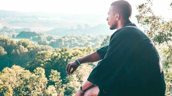man sitting on cliff overlooking trees